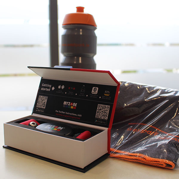 westpark fitness membership myzone belt in a white box along with grey and orange westpark fitness towel and water bottle on a table