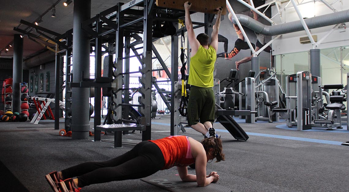 westpark fitness membership gym floor showing a male gym member doing a pullup and a female gym member doing a plank