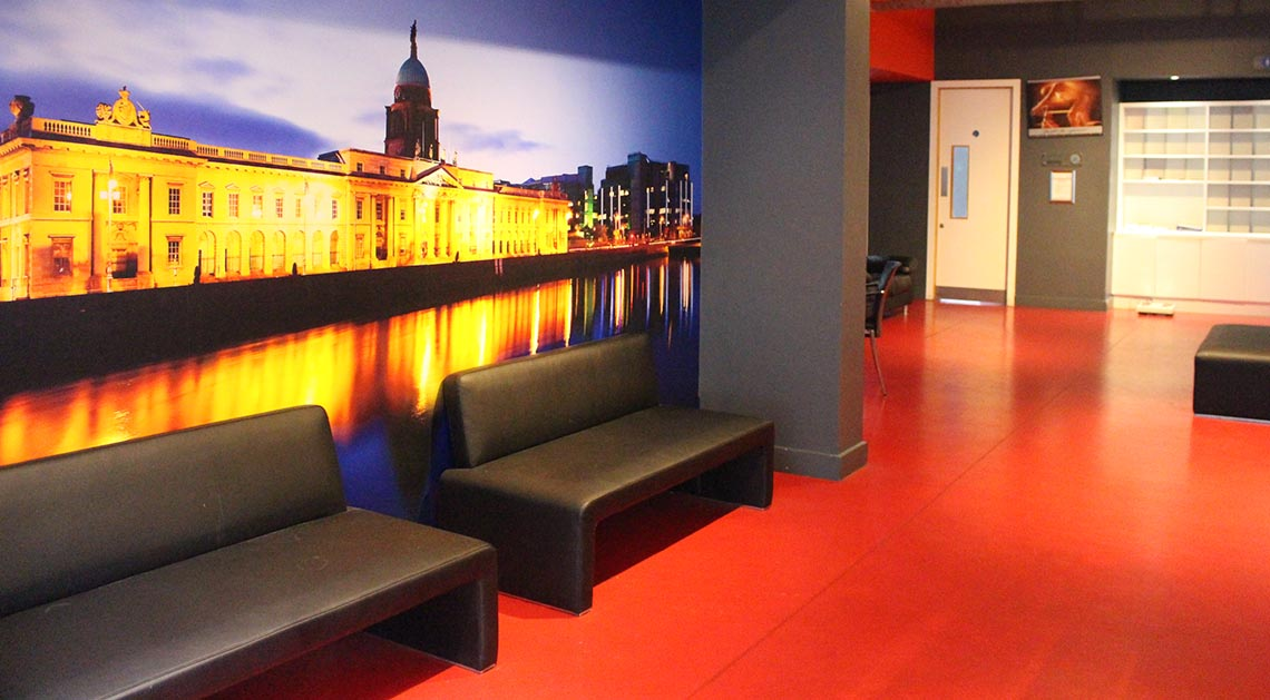 westpark fitness membership seating area with two leather couches and image of dublin skyline on the wall