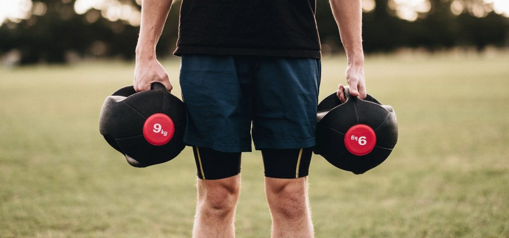 a man holding a medicine ball in each hands to complete the farmers walk exercise