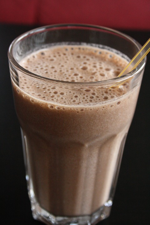 chocolate hazelnut smoothie pictured in a clear glass containing a clear straw