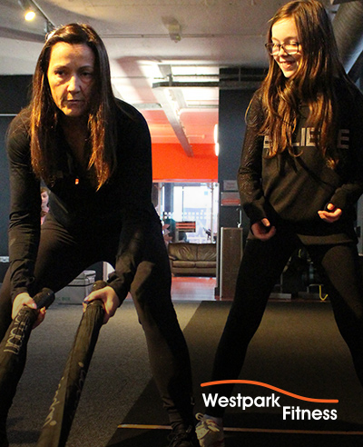 battle ropes westpark fitness trainer showing a child how to use them on the gym floor