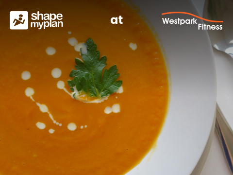 roasted sweet potato and carrot soup in a white bowl garnished with cream