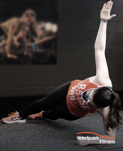 side plank exercise female gym goer at westpark fitness on her side on an exercise mat completing side plank exercise
