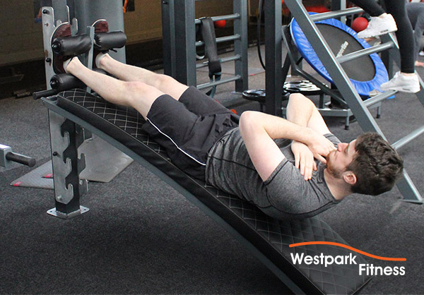 sit up bench image of male personal trainer raising up from grey sit up bench in gym
