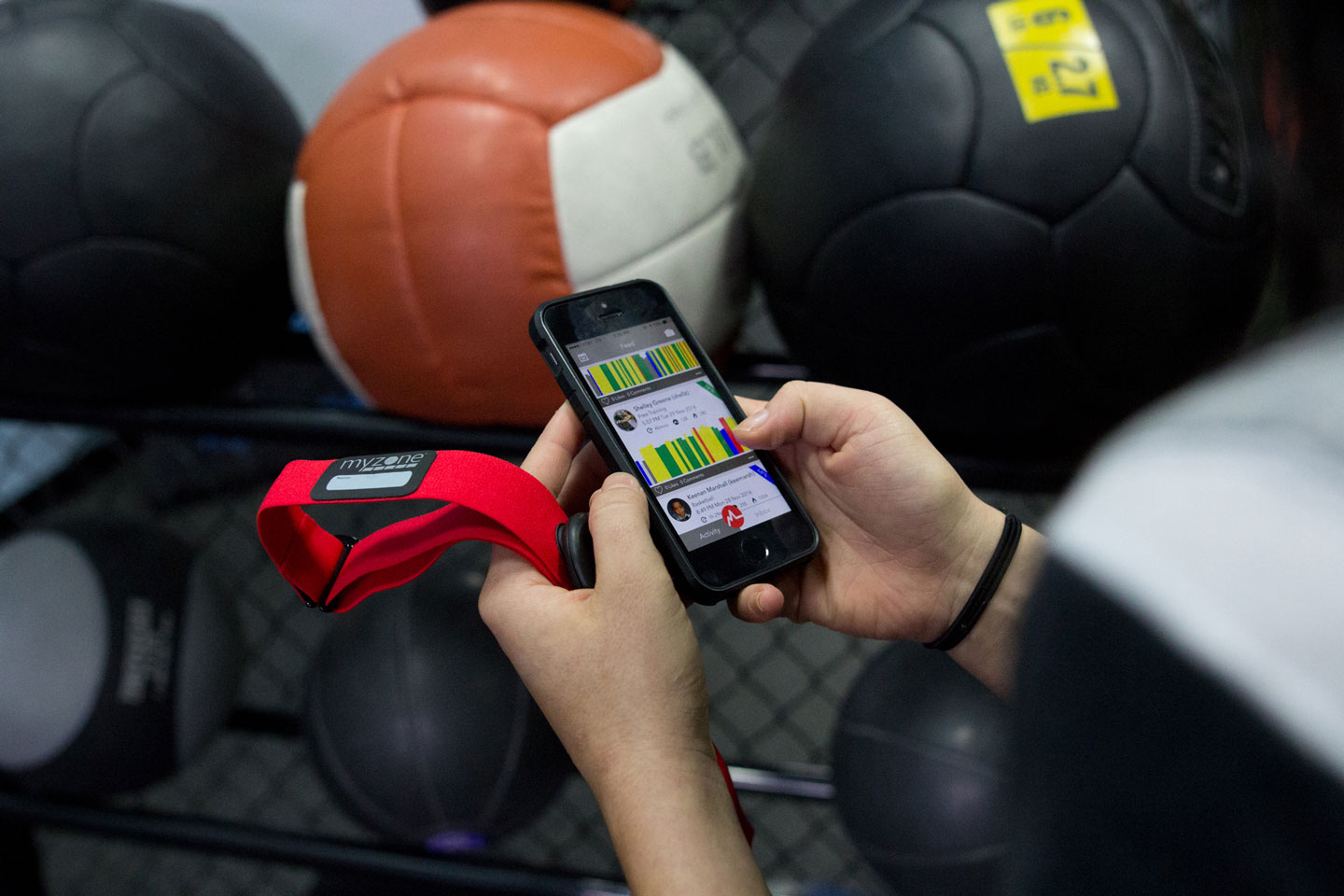 myzone classes at westpark fitness hands holding a smartphone and a red myzone fitness tracker belt in a gym