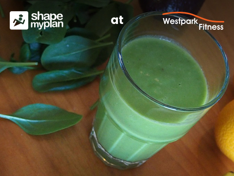green detox smoothie westpark fitness image of glass filled with a bright green smoothie on a wooden counter decorated with leaves