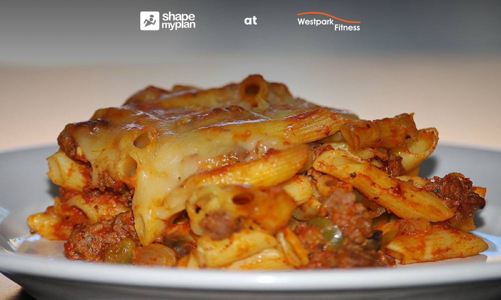 vegetable pasta bake by shape my plan at westpark fitness showing a white plate of pasta cheese and vegetables
