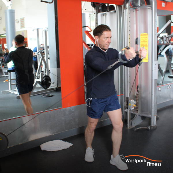 chest cable raise exercise at westpark fitness man standing in cable pulley machine holding both cable handles up at his shoulders