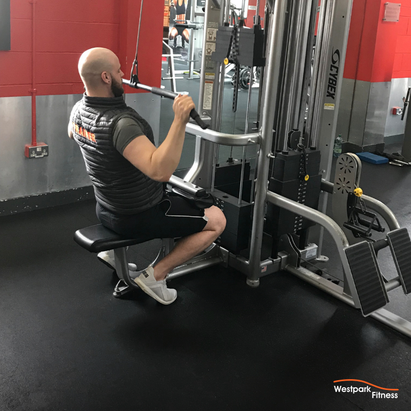 lat pulldown male gym goer sitting on the lat pulldown machine in westpark fitness with the handlebar down at his chest