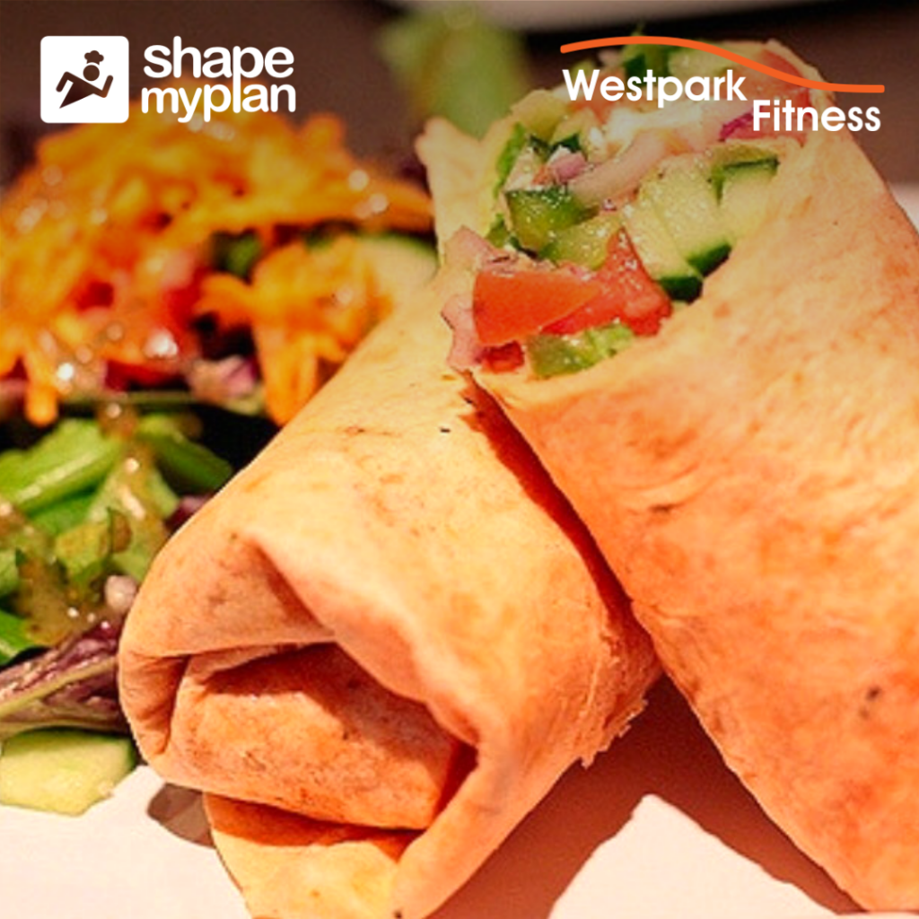 tuna salad wrap recipe from shape my plan at westpark fitness two wholemeal wraps wrapped up on a white plate showing tuna filling and a side salad