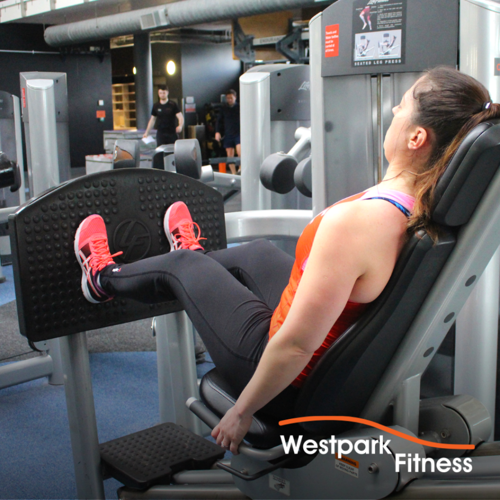 seated leg press exercise at westpark fitness female gym goer sitting in machine with feet up on the foot plate