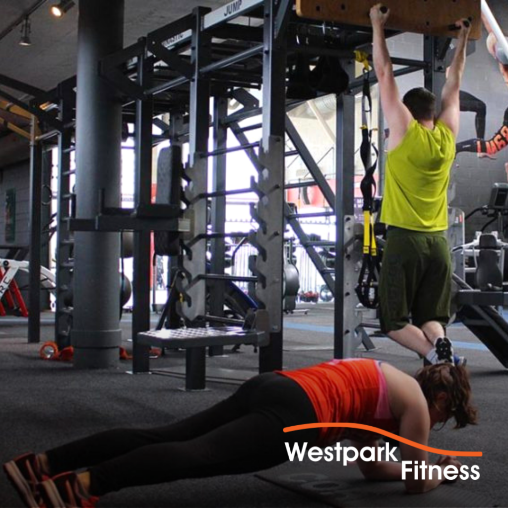 plank exercise at westpark fitness female gym goer in plank position on the ground and male gym goer hanging from pullup bar