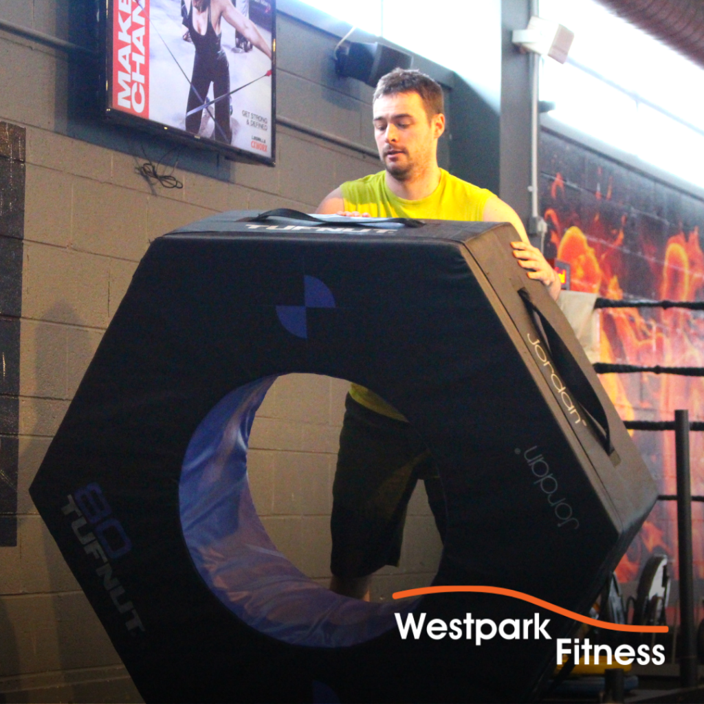 tyre flip exercise at westpark fitness male gym goer standing behind foam tyre about to push it on the ground