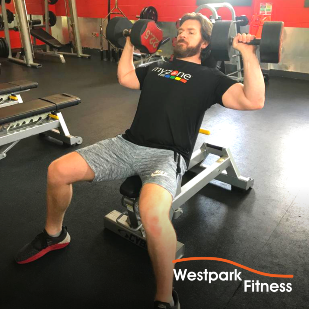 westpark fitness dumbbell shoulder press exercise male gym goer sitting on a bench holding a dumbbell at each side of his head