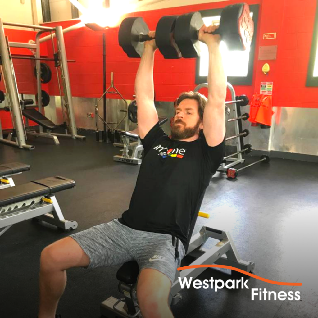 westpark fitness dumbbell shoulder press exercise male gym goer sitting on a bench holding two dumbbells over his head