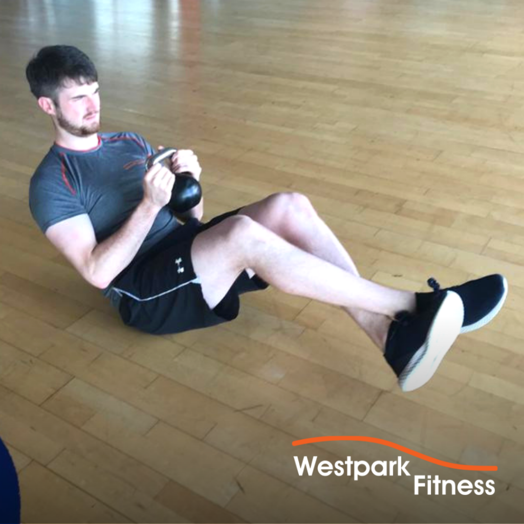 kettlebell russian twsit exercise being completed by a male gym goer lying on a wooden floor with a kettlebell gripped by both hands