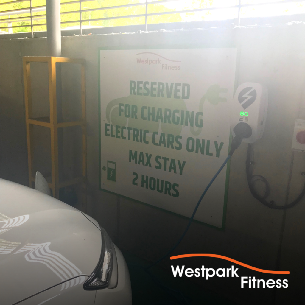 environmentally friendly gym in dublin electric car charger station with front of white car visibly plugged into it