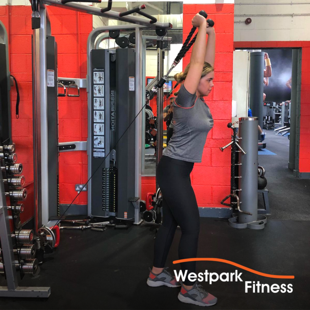 cable triceps extension exercise at westpark fitness female gym goer standing in front of a cable pulley machine holding a rope attachment behind her head
