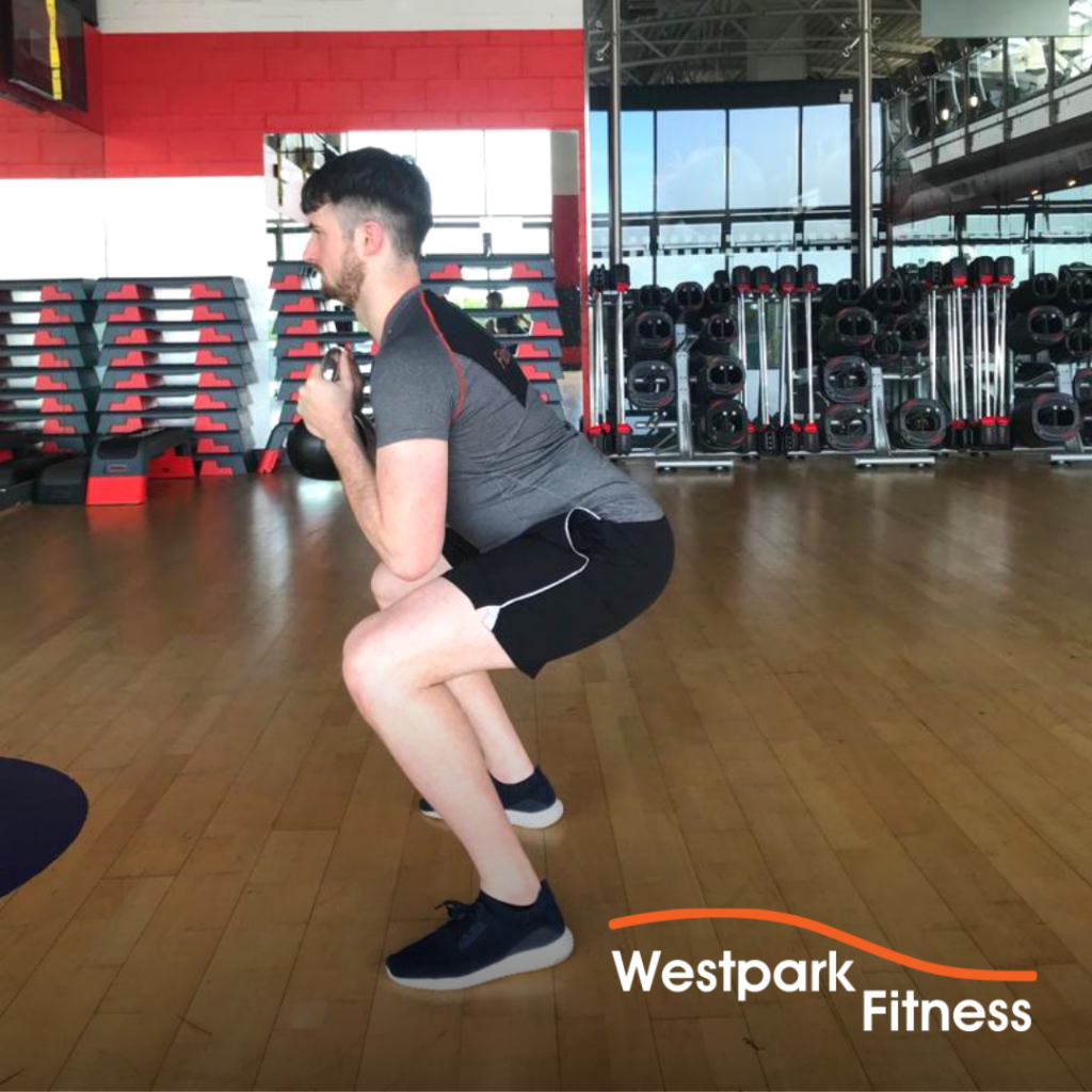 male gym goer in a squat position holding a kettlebell to complete the goblet squat exercise at westpark fitness