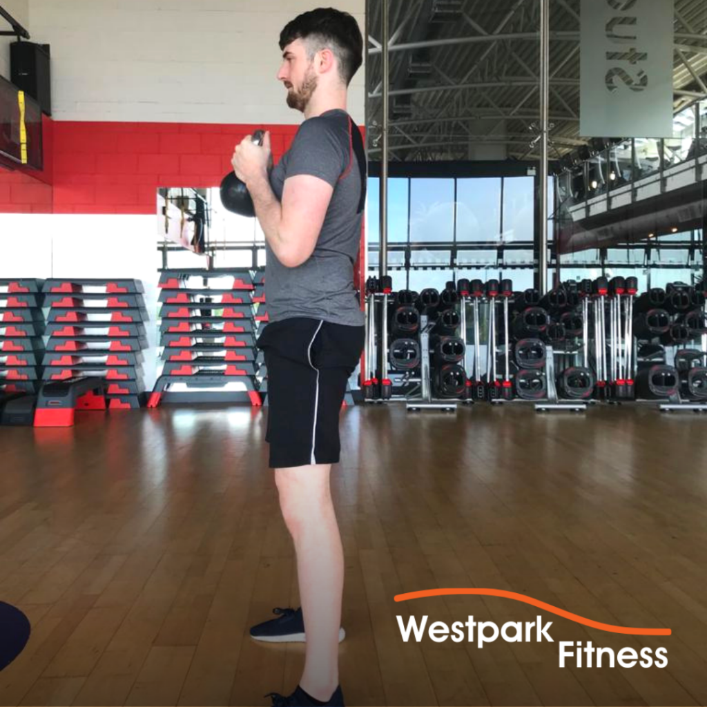 male gym goer standing up straight and holding a kettlebell to complete the goblet squat exercise at westpark fitness