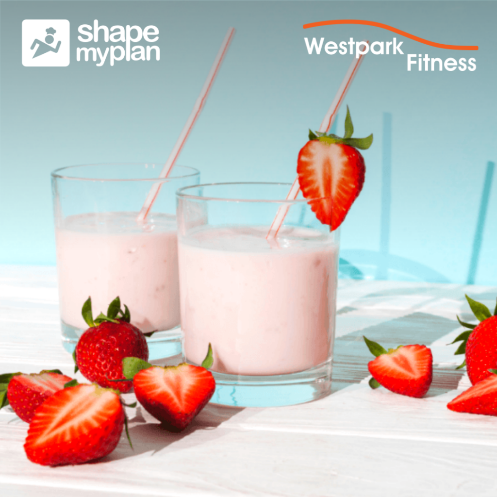 strawberry protein smoothie two classes filled with a pink stawberry smoothie surronded by strawberries on a white table