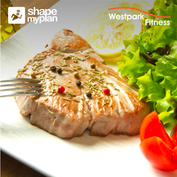 grilled tuna steak on a white plate beside a lemon and tomato and lettuce leaves