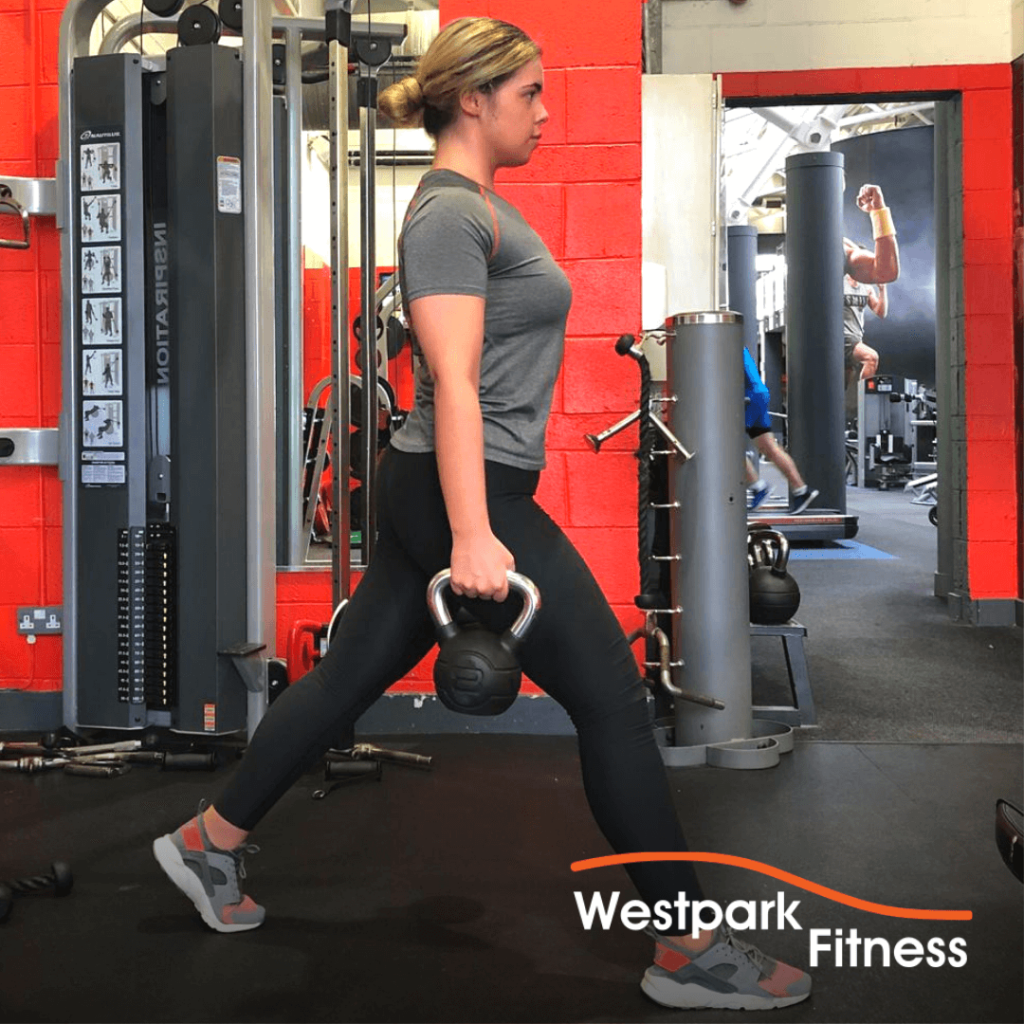 gym routine woman standing with a kettlebell in each hand