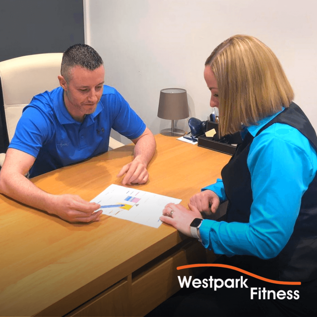 gym routine image of man and woman sitting a wooden table looking at a document